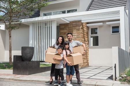 moving day. happy asian family in front of their new house