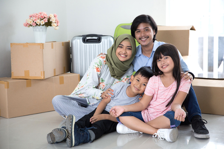 parent and kids with cardboard box. moving to new house