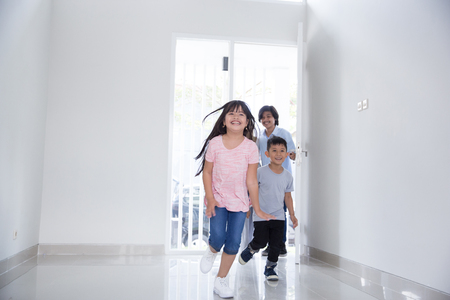 family with two kids entering their new house Foto de archivo