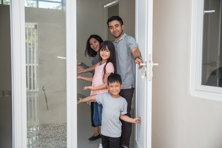happy family with kids open their house door