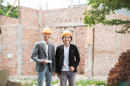 architect and builder standing in front of unfinished house