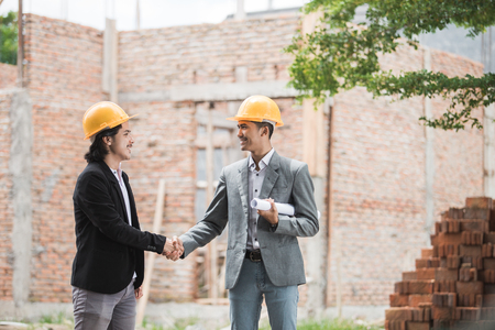 designers discussing construction plan shaking hand Stock Photo
