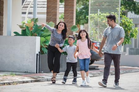 jonge en gelukkige Aziatische familie die samen loopt