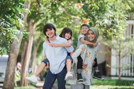 dos niños con sus padres a cuestas