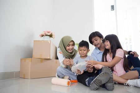 家族は新しい家に色のペンキを選ぶ