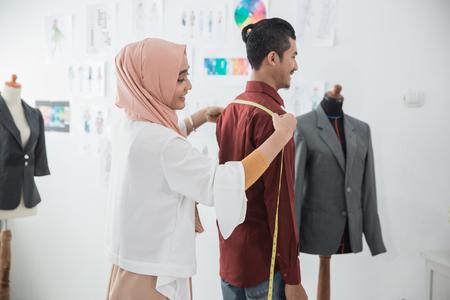 female fashion designer take a measure for clothing Reklamní fotografie