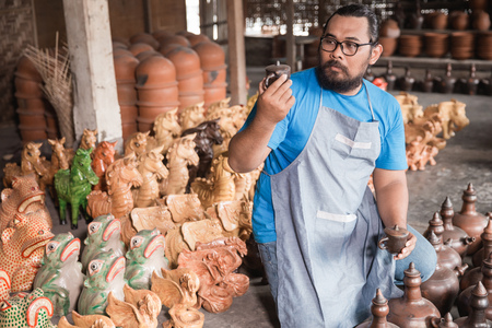 Pottery maker looking at product Stock Photo