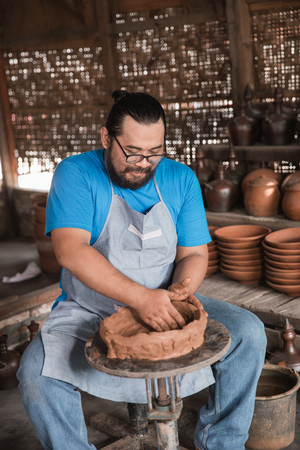 happy pottery maker creating a beautiful ceramic vase in his workshop Archivio Fotografico - 102120606