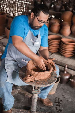 happy pottery maker creating a beautiful ceramic vase in his workshop