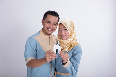muslim asian couple holding home sign Stock Photo