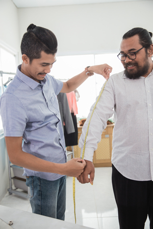 fashion designer taking measure of customer body
