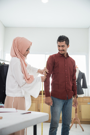 fashion designer taking measure of customer body