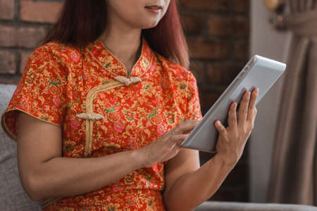 Close up asian woman wearing red dress sitting holding tablet