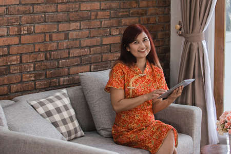 Attractive asian woman wearing red dress sitting holding tablet Stock Photo