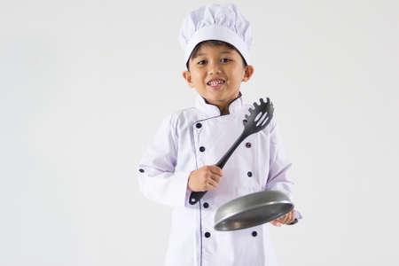 Netter Junge in der Kochuniform auf weißem Hintergrund