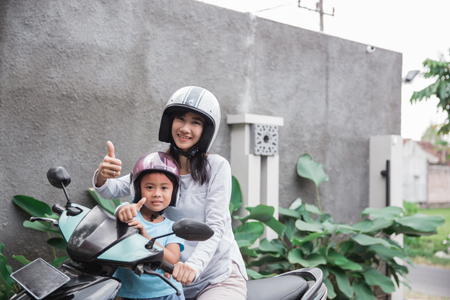 mother and daughter riding motorbike scooter