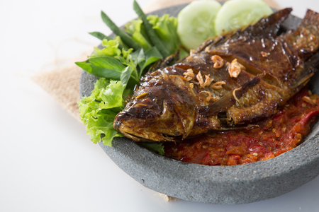 fish served with hot chili sauce or sambal in traditional grinder. indonesian food