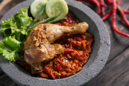 close up of ayam penyet traditional spicy sauce or sambal. fried chicken