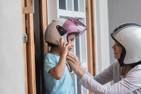 young happy little girl wearing helmet with her mother Foto de archivo