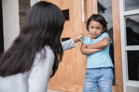 Porträt der jungen Mutter überzeugte ihre Tochter. Verhaltensproblem des Kindes Standard-Bild