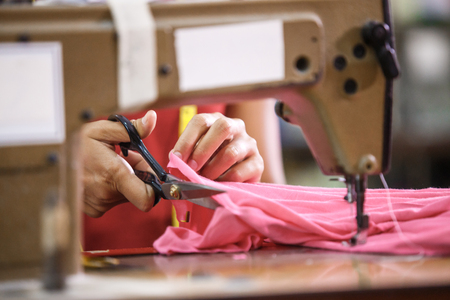 mans hands cutting a fabric at a clothing factory