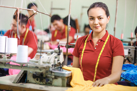 Seamstress in textile factory sewing using industrial sewing machine