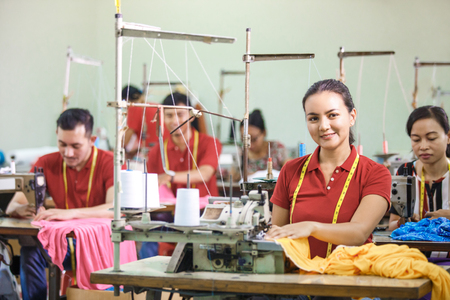 asian workers in garment factory sewing with industrial sewing machine