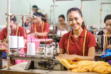 Sarta in fabbrica tessile sorridente durante la cucitura