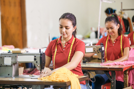 asian seamstress in garment factory sewing with industrial sewin Standard-Bild
