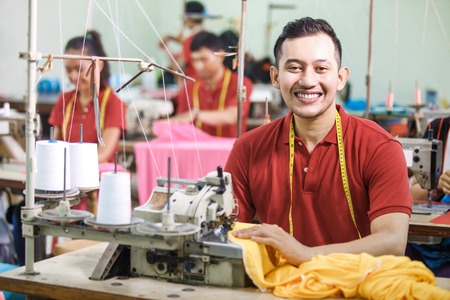 asian worker in textile factory sewing using industrial sewing machine