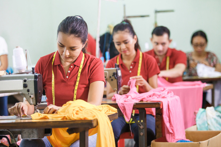 asian workers in garment factory sewing with industrial sewing m Foto de archivo