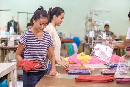 arbeiders in textielfabriek die hun producten verpakken