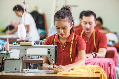 Seamstress in textile factory sewing with industrial sewing mach