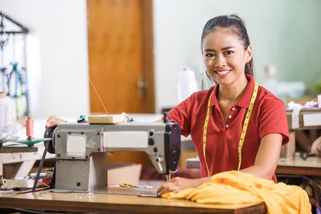 Seamstress in textile factory smiling while  sewing with industr Stockfoto