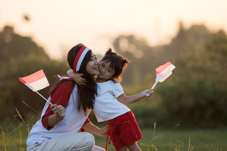 mother and daughter raising flag of indonesia