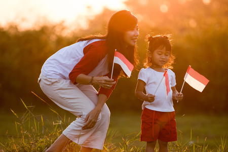 mom and kid together with indonesian flag