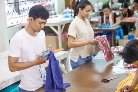 Arbeiter bei Textilunternehmen, die ihre Produkte kennzeichnen und verpacken
