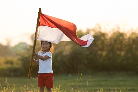 kids raising indonesian flag Banque d'images - 105336103