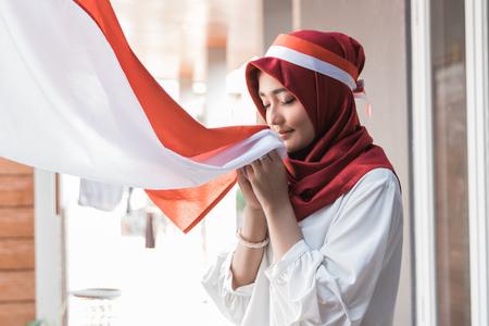donna con sciarpa che bacia la bandiera dell'Indonesia Archivio Fotografico