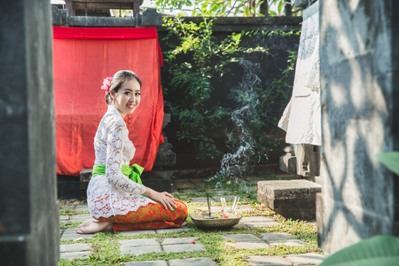 balinese woman smiling after praying at temple on small shrines Stock Photo