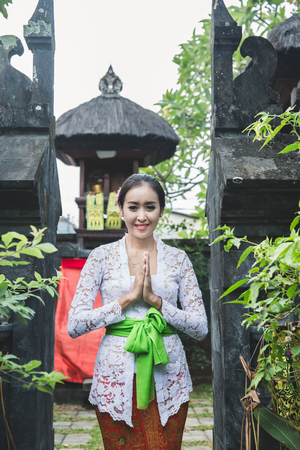 balinese woman with traditional clothes and welcome gestures smi Stock fotó - 105484747