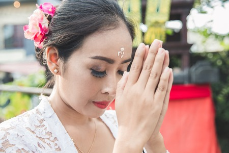 balinese woman praying at temple on small shrines in houses Stock Photo