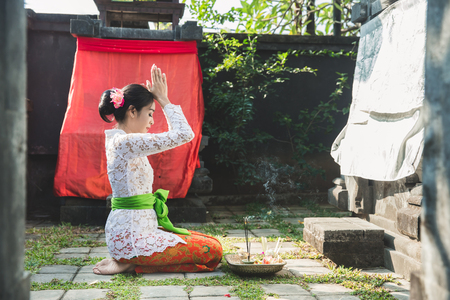 balinese woman praying at temple on small shrines in houses 스톡 콘텐츠