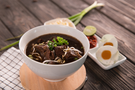 Traditional Indonesian beef black soup served in a bowl on a wooden table background