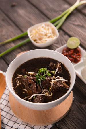 Traditional Indonesian beef black soup served in a bowl on a wooden table background Archivio Fotografico - 105519461
