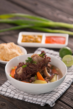 Oxtail soup served in a bowl on a wooden table background