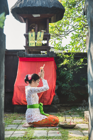 portrait of balinese woman praying at temple on small shrines in houses 스톡 콘텐츠 - 105571638