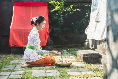 balinese woman praying at temple on small shrines in houses Фото со стока