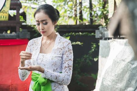 balinese woman doing ritual praying at temple