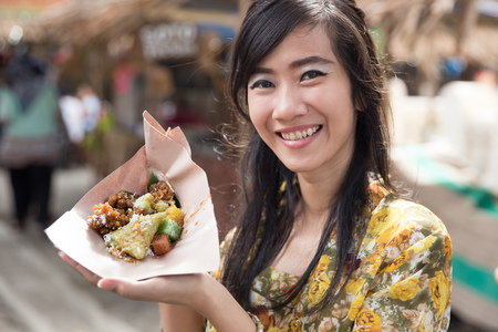 woman in kebaya showing traditional food Stock Photo